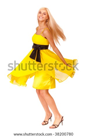 Beautiful blonde in yellow dress with black belt is joyfully turned, it is isolated on white background.