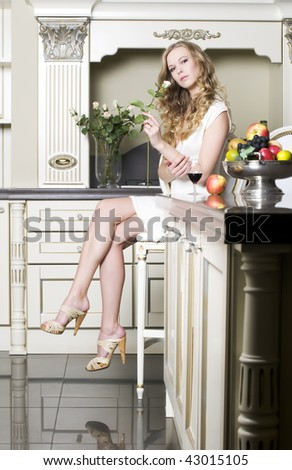 Beautiful blonde is smelling a rose at her kitchen - stock photo