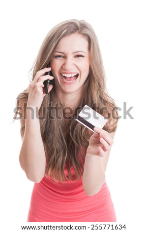 Beautiful blonde lady showing a credit or debit card while talking on the phone - stock photo