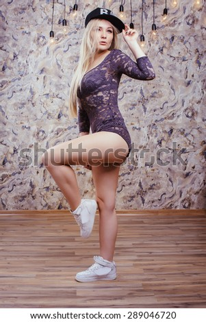 Beautiful blonde lady with long straight hair in lacy combidress, white sneakers and black hat. With sexy slim body. Posing indoors. - stock photo