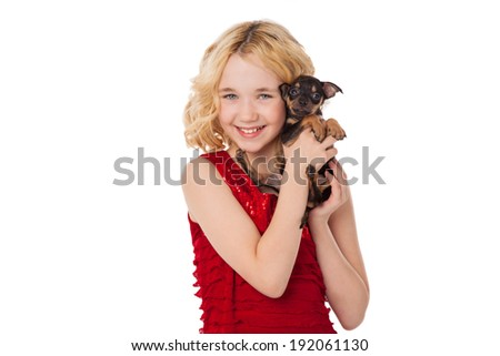 beautiful blonde little girl holding  puppy wearing red dress - stock photo