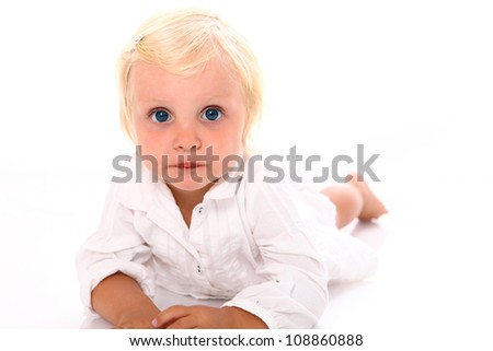 Beautiful blonde little girl  lying on the floor and looking directly into the camera on white background close-up