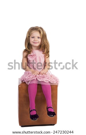 Beautiful blonde little girl with pink dress sitting on cube over white background  - stock photo