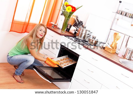 Beautiful blonde long haired woman taking out from oven a tray of fresh cookies