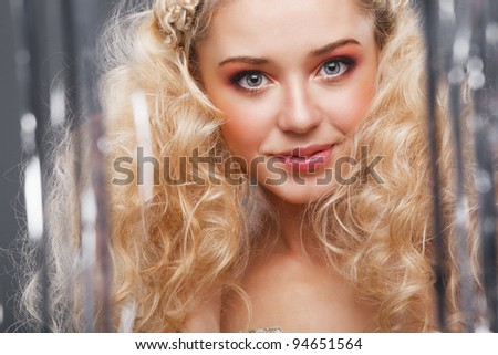 Beautiful blonde looking at the camera through the curtains of silver