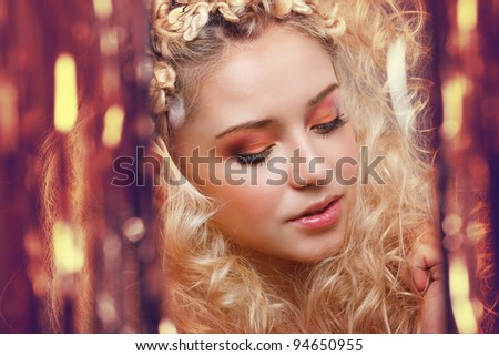 Beautiful blonde looking through the golden curtains