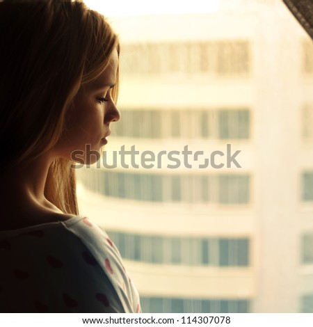 beautiful blonde looks out the window - stock photo