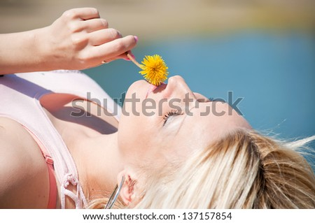 Beautiful blonde lying and smelling yellow dandelion, in the park by the lake - stock photo