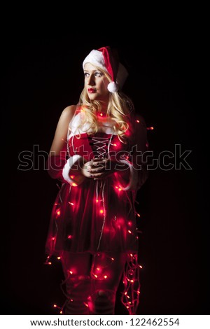 Beautiful blonde model, dressed in a Christmas outfit, covered in red twinkling Christmas lights.