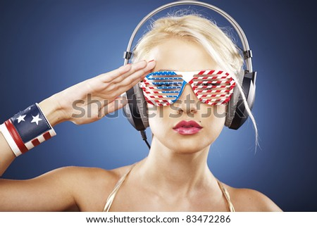 Beautiful blonde model with headphones and American inspired grid glasses dressed in gold swimwear saluting the flag. - stock photo