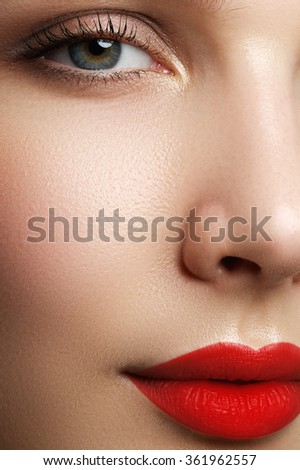 Beautiful blonde model woman face with blue eyes and perfect make-up isolated on white background. Portrait of beauty young blond girl with red lips. Female face with clear skin close-up. Skincare