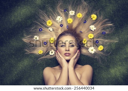 beautiful blonde naked female posing lying on green meadow with colorful flowers in the long smooth hair, fresh style, funny spring portrait  - stock photo