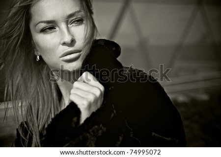 Beautiful blonde near a modern building from glass. Sepia photo. - stock photo