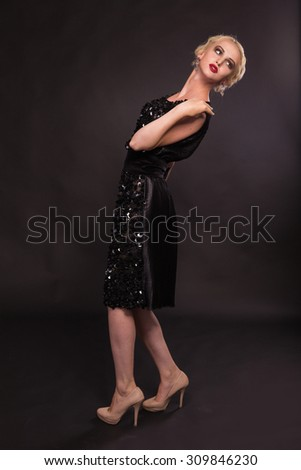Beautiful blonde on a black background. A model posing in a beautiful dress. Beautiful jewelry and dress.