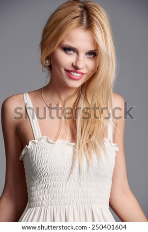 Beautiful blonde on gray background studio portrait