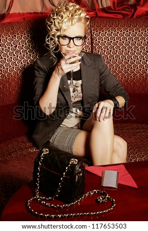beautiful blonde party girl drinking martini on the red sofa in the club. Indoor shot