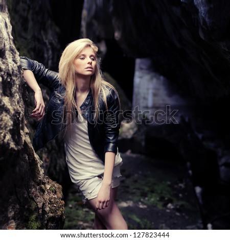 beautiful blonde posing on a rock background - stock photo