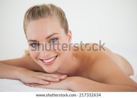 Beautiful blonde relaxing on massage table smiling at camera at the health spa - stock photo
