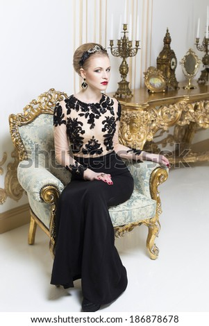 Beautiful blonde royal woman sitting on a retro chair in gorgeous luxury dress. Indoor - stock photo