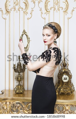 Beautiful blonde royal woman standing near retro table in gorgeous luxury dress with mirror in her hands. Indoor - stock photo