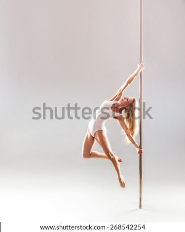Beautiful blonde sexy pole dance woman. - stock photo