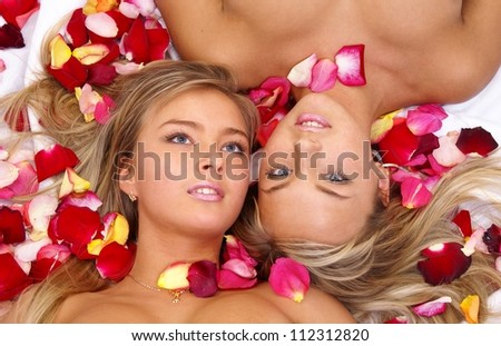 Beautiful blonde sisters twins lying in red rose  petals - stock photo
