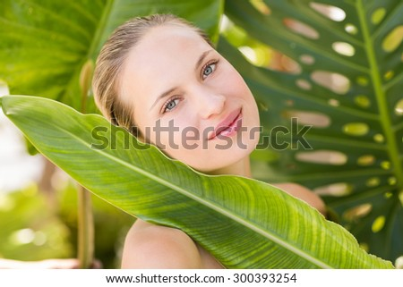 Beautiful blonde smiling at camera behind leaf at the health spa - stock photo