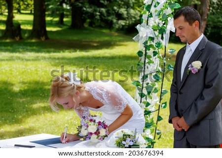 beautiful blonde smiling bride signed wedding contract against green grass outdoor, groom looking on her - stock photo