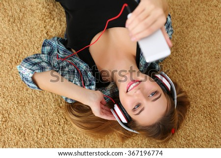 Beautiful blonde smiling woman lying on carpet floor wearing headphones, holding cell phone and listening music portrait. Modern urban life, audio book, radio or education concept - stock photo