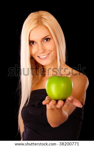 Beautiful blonde stretches green apple, it is isolated on black background.