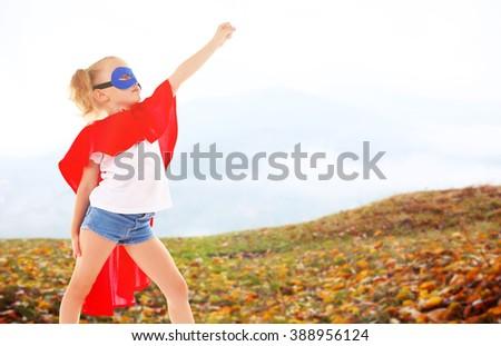 Beautiful blonde superhero little girl on mountains background - stock photo