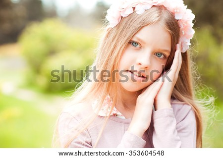 Beautiful blonde teen girl 10-14 year old wearing floral wreath outdoors. Posing over green nature background. Looking at camera. Teenager hood.