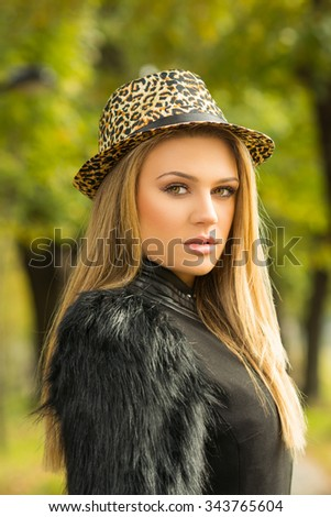 Beautiful blonde teenage girl in fur coat and leopard print fedora hat in park in autumn. Portrait of attractive young woman in fall. Vertical, retouched, vibrant colors. - stock photo