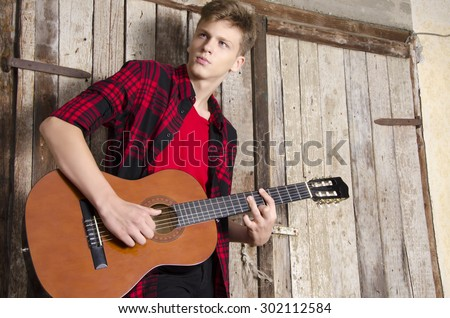 Beautiful blonde teenager playing classic guitar, grungy old door in background