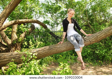 Beautiful blonde teenager si on a huge branch tree