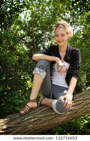 Beautiful blonde teenager sit on a tree