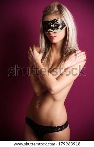 Beautiful blonde topless in a black panties with eye mask posing on a purple background, in the studio, glamour photography - stock photo