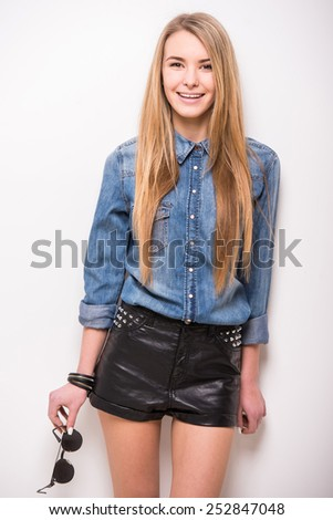 Beautiful blonde, trendy girl with sunglasses is posing on white background. - stock photo