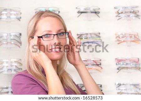 beautiful blonde tries on glasses - stock photo