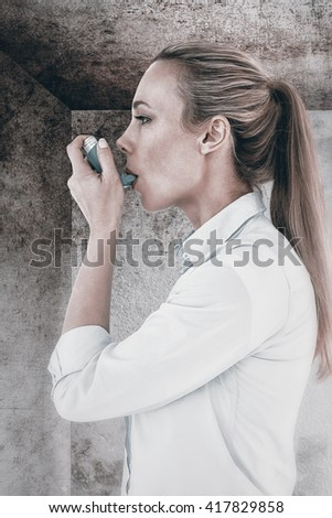 Beautiful blonde using an asthma inhaler against image of room corner - stock photo