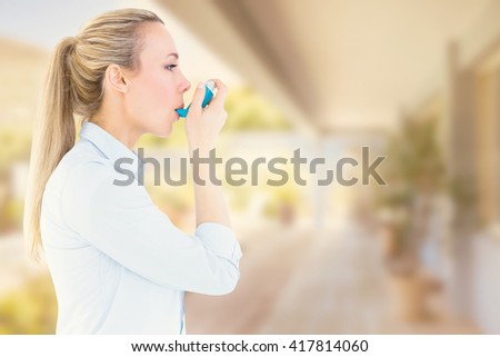 Beautiful blonde using an asthma inhaler against stylish outdoor patio area - stock photo