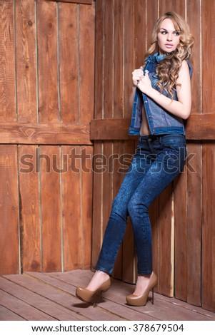 Beautiful blonde wearing jeans suit posing near wooden wall - stock photo