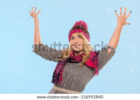 Beautiful blonde who is wearing a red knitted hat and a scarf and feeling excited about snow over a blue background