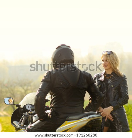 Beautiful blonde with a biker posing near a sports bike. Beautiful couple with a motorcycle at sunset - stock photo