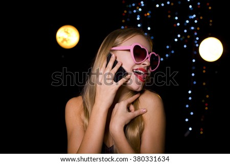 beautiful blonde with a mobile phone on a black background - stock photo