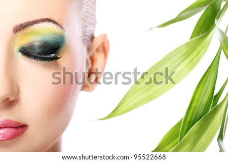 Beautiful blonde with artistic make- up and  bamboo leaves - stock photo