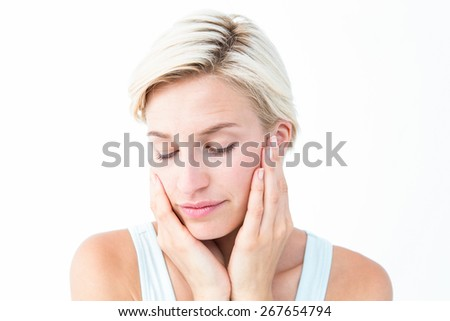 Beautiful blonde with eyes closed touching her cheeks on white background - stock photo