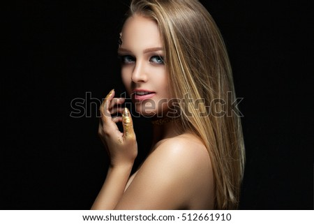 beautiful blonde with golden make-up. Beauty fashion. Face close-up portrait on a dark background.
