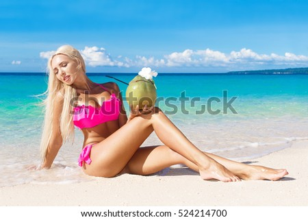 Beautiful blonde with long hair in bikini with coconut on a tropical beach. Blue sea in the background. Summer vacation concept.