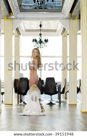 Beautiful blonde with mink coat in the restaurant - stock photo